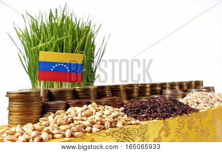 Venezuela Flag Waving With Stack Of Money Coins And Piles Of Wheat And Rice Seeds