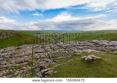 View of the Yorkshire dales over the rocky Malham cove with a cloudy sky