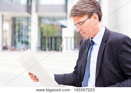 businessman in frankfurt main, reading the newspaper