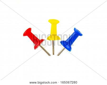 Three colored drawing pins inserted in the light background