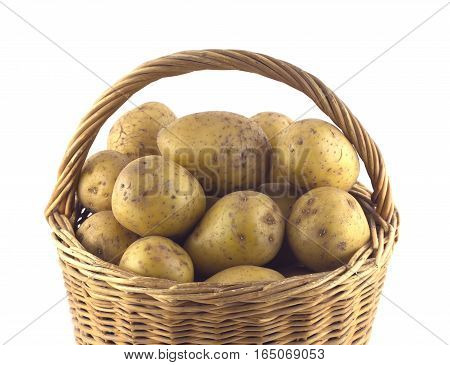 Lot of ripe potatoes in brown wicker basket isolated on white closeup