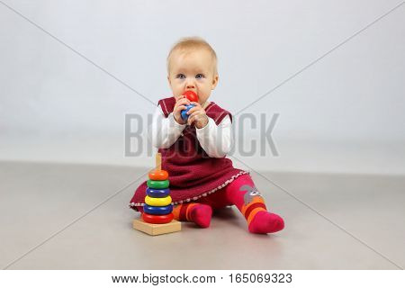 Shot of an adorable baby girl in red clothes playing with some wooden toys.