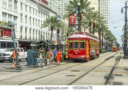 NEW ORLEANS - JULY 16 2013: people travel with the old Street car Canal street line St. Charles line in New Orleans USA. It is the oldest continually operating street car line in the world.