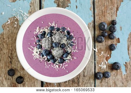 Healthy Smoothie Bowl With Blueberries, Dragon Fruit And Coconut, Above View On Rustic Blue Wood