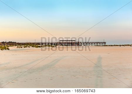 romantic sunset at the ebach with wooden pier at Dauphine Island