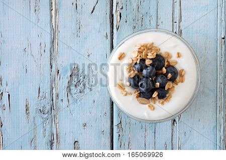 Greek Yogurt With Blueberries And Granola, Downward View On A Rustic Soft Blue Wood Background