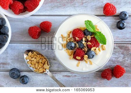 Greek Yogurt With Sweet Berries And Granola, Overhead Scene On Rustic Wood