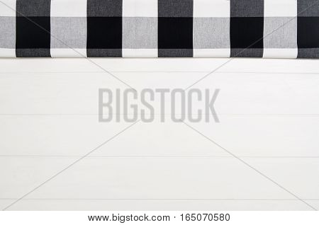 Top view of black checkered napkin or tablecloth on white wooden table with visible planks, texture and copy space for text.