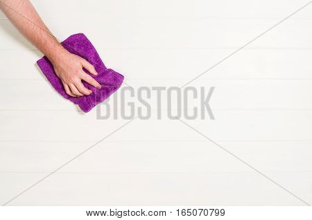 Man's or woman's hand cleaning with microfiber cloth on a white wooden floor background.