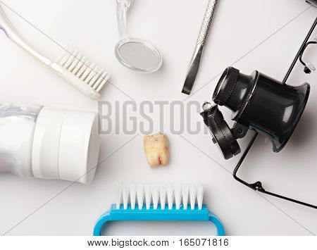 Extracted teeth around dental tools isolated on white background