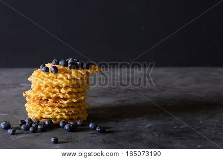 Waffles. Stack Belgian waffles with blueberries on a dark gray background. Sweet food concept. Copy space. Fresh blueberries.