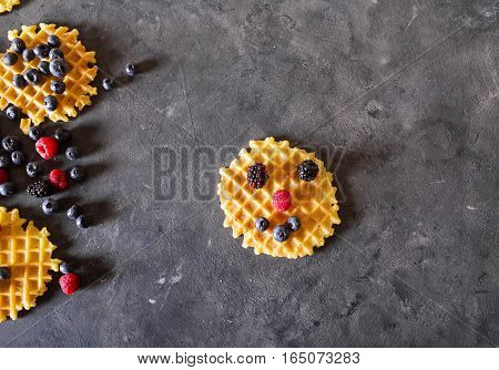 Belgian waffles with berries on the gray background. Sweet food concept. Copyspace. Fresh berries raspberries blueberries blackberries. waffle with smile face. Funny waffle. Top view flat lay