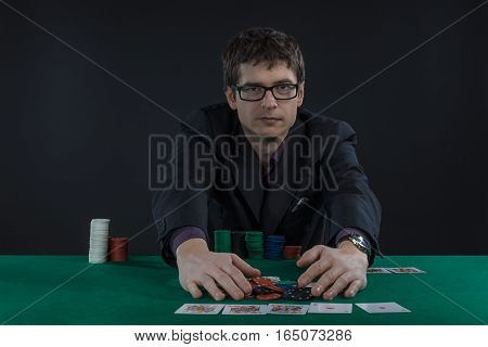 male player in suit and glasses playing poker