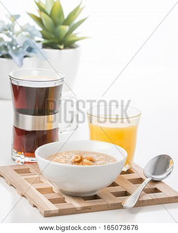 Bowl of maple walnut flavored oatmeal with coffee and juice.