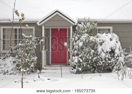Red door and snow covered house Gresham Oregon.