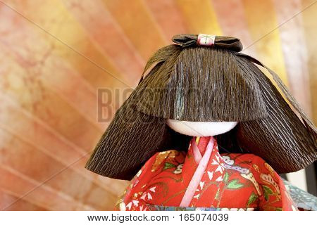 A Japanese doll before a brown and gold fan as background.