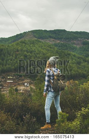 Young woman traveler in chekered shirt and blue jeans hiking in mountains, Dim Cay district of Alanya, Antalya province, Mediterranean Turkey