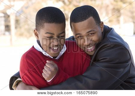 African American teenage brothers smiling and laughing.