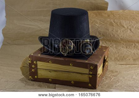 wooden box, hat and glasses on Steam punk background of crumpled paper. Steam punk hat and sunglasses.