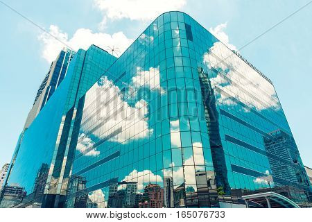 Modern glass building skyscrapers with blue cloudy sky reflection. Business district background.