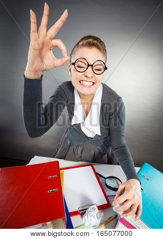 Job success celebration promotion concept. Cheerful office lady at desk. Secretary making ok gesture smiling while at work.