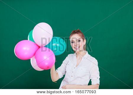 Teenage joyful girl playing with colorful balloons. Holidays celebration and lifestyle concept. Studio shot on green