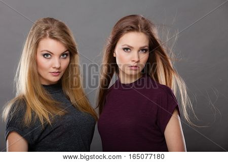Family relationships friendship concept. Two beautiful women sisters blonde and brunette with windblown hair posing charmingly. Studio shot on dark grey background