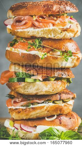 Heap of Bagels with salmon, eggs, vegetables, capers, fresh herbs and cream-cheese, grey concrete background, vertical composition. Healthy breakfast, lunch or take-away food concept
