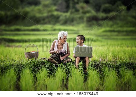 Happy boy and grandmother using laptop asia thailand.