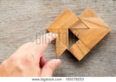 Man held piece of tangram puzzle to fulfill the heart shape on wooden table
