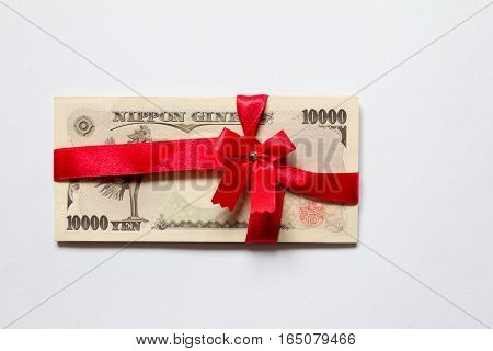 Japanese yen with the red bow on white background (Concept for corruption)