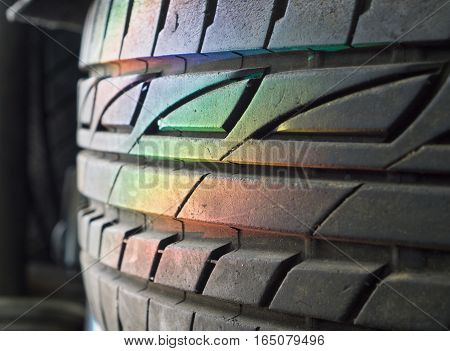 Spectrum rainbow light on stack of car wheels