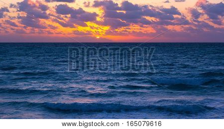 Sunset over the ocean with violet clouds. Scenic sunset over the ocean.
