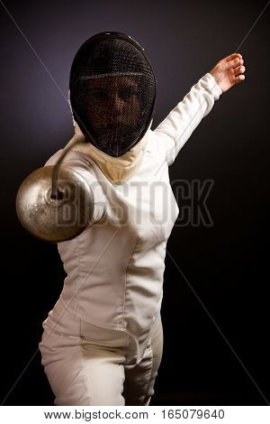 woman dressed in a fencing suit and mask, pointing her rapier at you