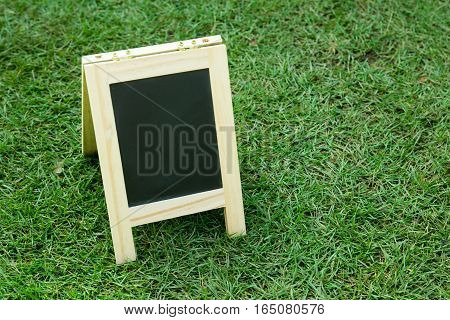 Blank black board with easel on green grass background