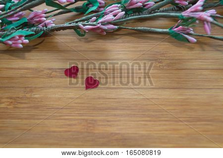 small red hearts on bamboo board with artificial pink flowers