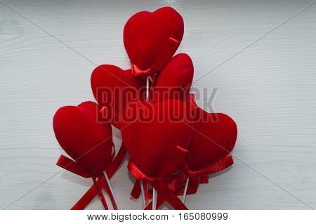 red velvet hearts on a stick on white wooden background
