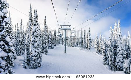 Riding the Chair Lift in a Winter Landscape on the Ski Hills near Sun Peaks village in the Shuswap Highlands of central British Columbia, Canada