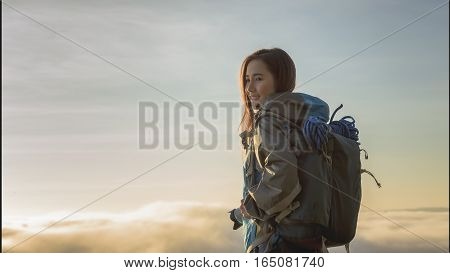 the tourist standing on cliff in front of a sunset and taking pictures of fog in mountain view around.View of mountains winter landscape with foggy hills at sunrise.
