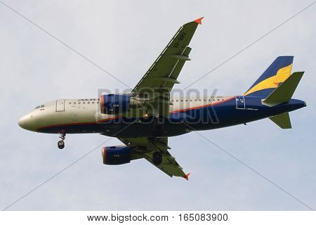 ST. PETERSBURG, RUSSIA - JUNE 24, 2016: The flying Airbus A319-112 plane (VP-BBU) of Donavia airline close up in the cloudy sky
