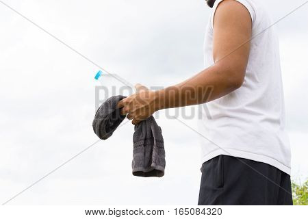 Man with water bottle and towel in his hand and nature background view.01