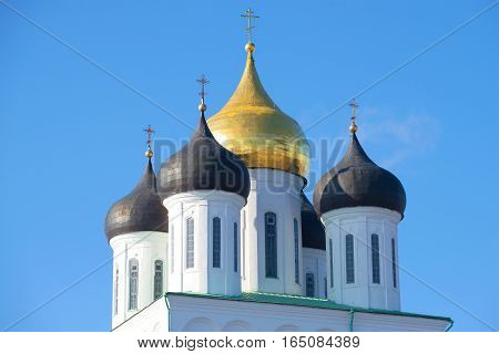 Domes of ancient Trinity Cathedral against the background of the blue sky. Pskov, Russia