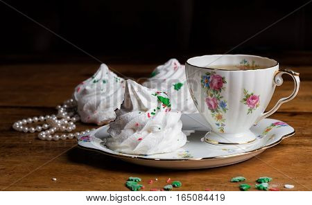 refined porcelain cup of tea and sauser with zephyr meringue marshmallow wood pearls
