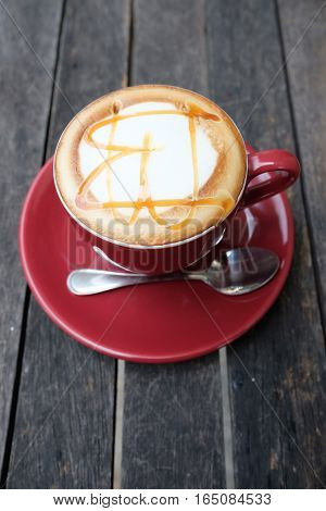Hot caramel macchiato on wooden table  in the big coffee shop