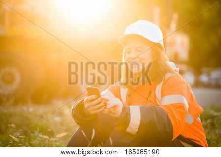 Senior woman engineer in protective workwear relaxing and looking to phone- outdoor at sunset