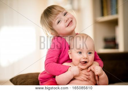 Litlle girl holding her baby brother - indoor home setting