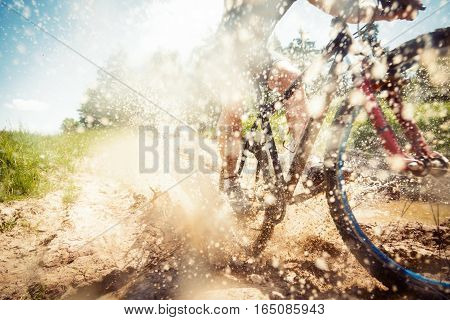 young man riding his mountain bike through a dirty puddle
