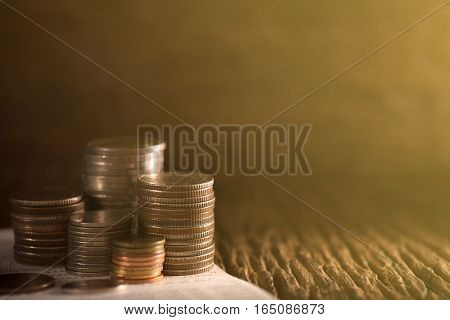 Row of coins and account book on the table with sunlight, banking and finance concept.