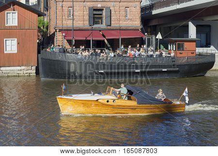 PORVOO, FINLAND - JUNE 13, 2015: Motor boat floats on the river on the background of the summer café of the ship. Old Porvoo, Finland