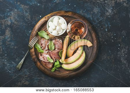 Prosciutto di Parma, cantaloupe melon, mozzarella cheese in bowl, fresh basil leaves and glass of rose wine in round serving tray over dark blue plywood background, top view, horizontal composition